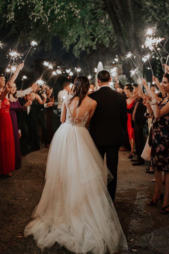 In questa foto due sposi vanno incontro agli ospiti che, alla fine del ricevimento, li aspettano sorridenti con le stelle filanti accesi nelle mani