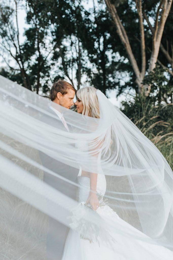 In questa foto due sposi in un bosco si guardano innamorati dietro al velo della sposa tirato in primo piano