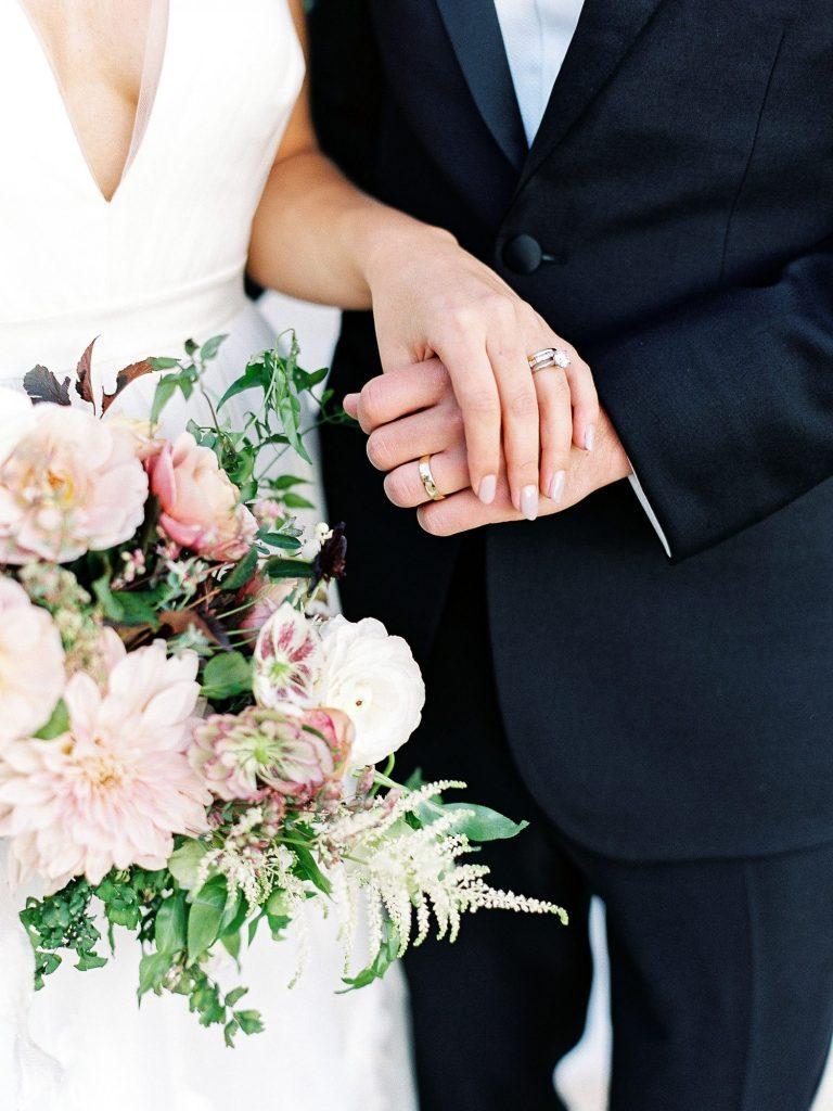 In questa il dettaglio delle mani strette di due sposi. L'attenzione si concentra sulle fedi e il bouquet di fiori rosa cipria della sposa