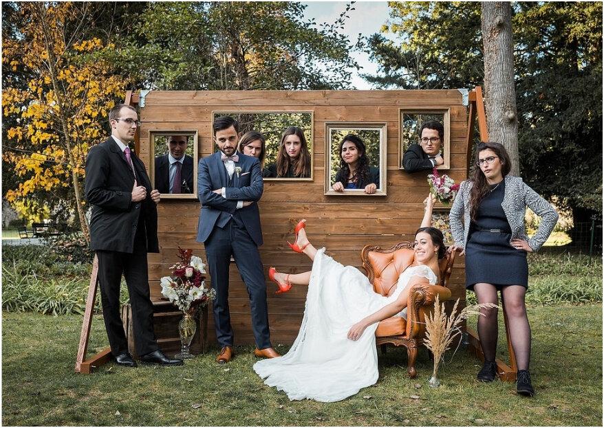In questa foto due sposi in una posa divertente insieme agli amici davanti ad un photo booth creato con uno steccato di legno e delle cornici su un prato. La sposa è seduta su una poltrona con le gambe e il bouquet alzati mentre lo sposo è in piedi. Accanto a loro due amici. Dalle cornici sbucano altri 5 amici
