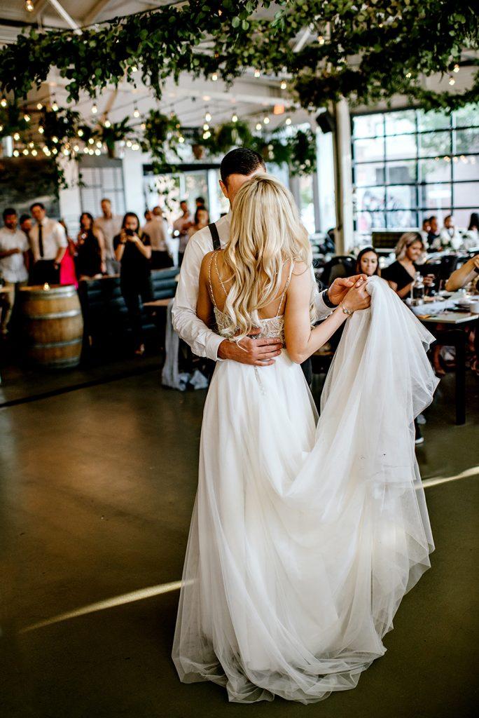 In questa foto due sposi durante il loro primo ballo al ricevimento di nozze mentre gli ospiti li guardano commossi