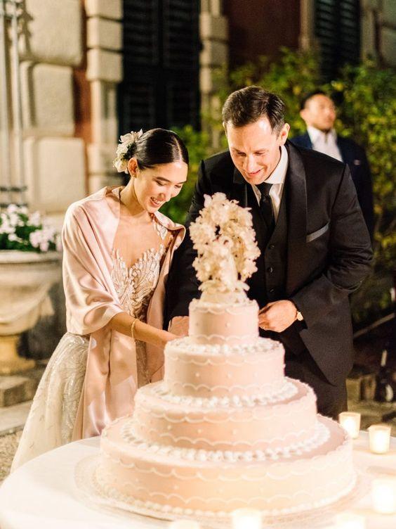 In questa foto due sposi sorridenti tagliano la loro torta nuziale a quattro piani, rosa e con un cake topper floreale ripresa in primo piano. La sposa indossa uno scialle in coordinato e capelli raccolti