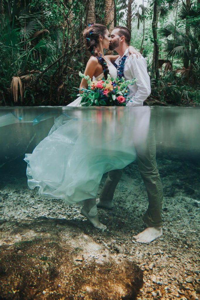 In questa foto due sposi posano mentre si baciano abbracciati dentro un lago immersi in acqua fino al busto. La sposa ha i capelli intrecciati con petali blu e tiene tra l mani un bouquet di foglie e fiori rosa, gialli e blu