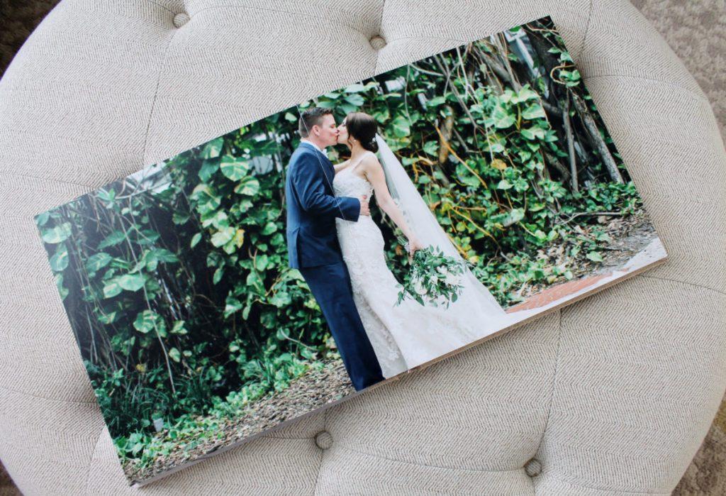 In questa foto un fotoalbum di matrimonio aperto sulla foto di due sposi che si baciano in un bosco e poggiato su un pouf beige