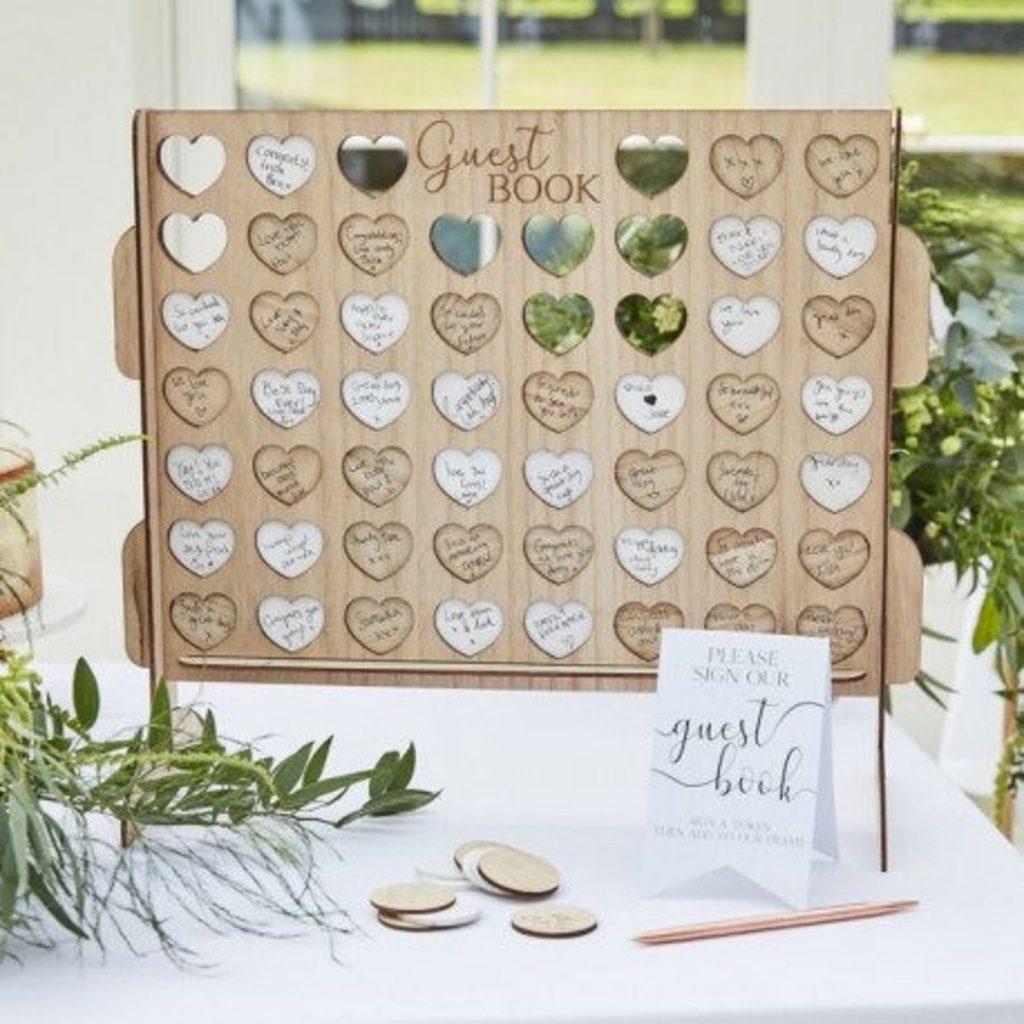 """In questa foto un guestbook, il libro per gli ospiti di un matrimonio, in legno che riproduce il gioco del """"Forza 4"""" con i tasselli a forma di cuore per un matrimonio a tema amore"""