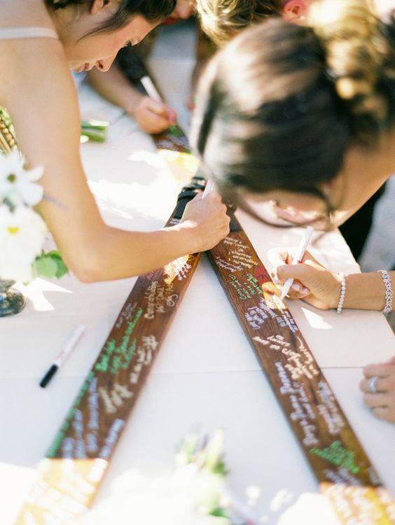 In questa foto alcuni ospiti di un matrimonio firmano un guestbook realizzato con due sci, perfetto per un matrimonio in montagna