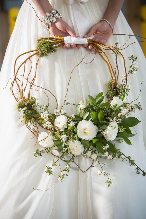 In questa foto un hoop bouquet, un bouquet da sposa a cerchio, realizzato con ramoscelli rampicanti e ranuncoli bianchi