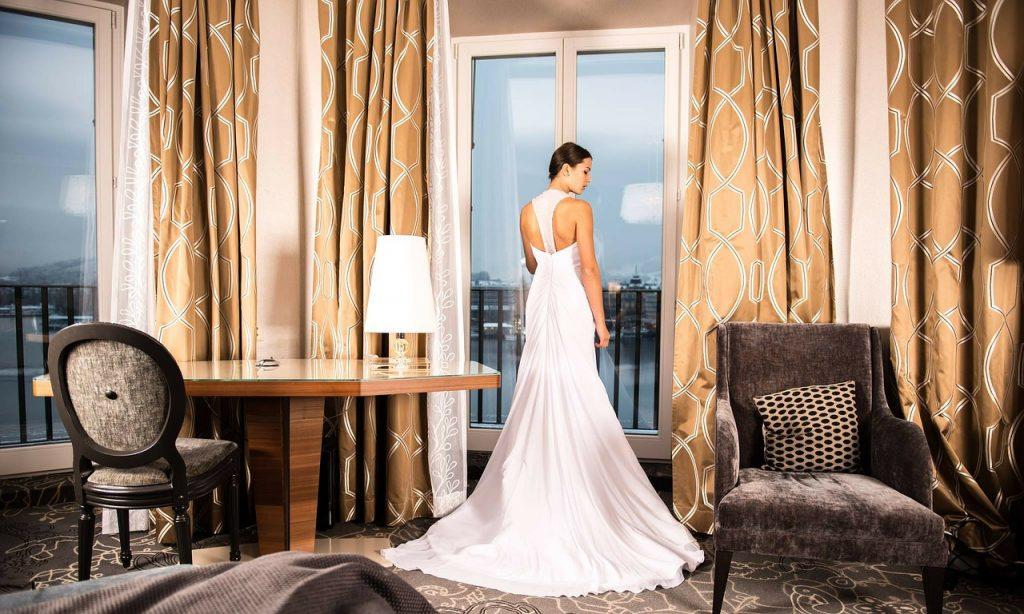 In questa foto una sposa ritratta di spalle, davanti alla finestra della sua camera di hotel