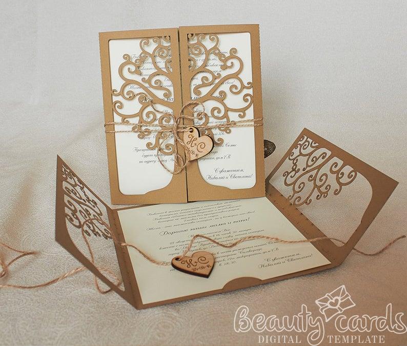 In questa foto partecipazioni in cartoncino beige e avorio intagliato a forma di albero della vita con chiusura in legno a forma di cuore
