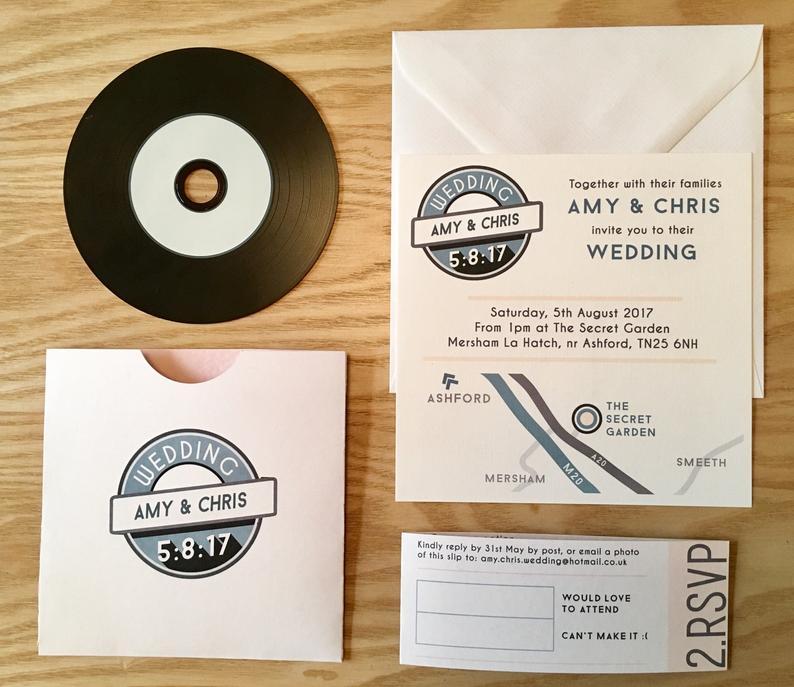 In questa foto partecipazioni per un matrimonio a tema musica con careta colore avorio e testi in nero e azzurro. Alla bustina è abbinato anche un disco in vinile