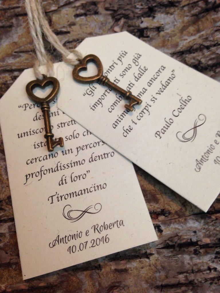 In questa foto segnaposto con cartoncini e chiavi in bronzo a forma di cuore riportano frasi d'amore di autori famosi e la data delle nozze degli sposi