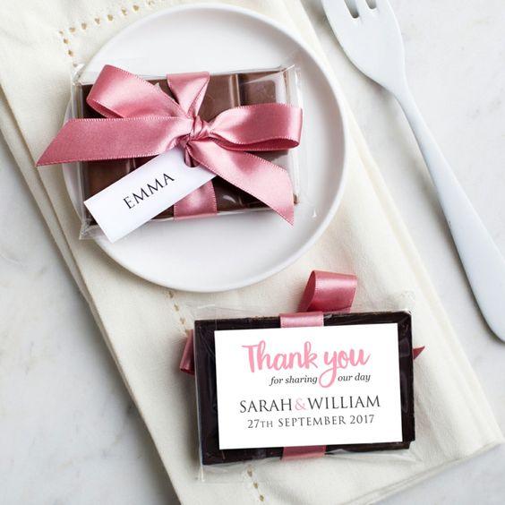 In questa foto una barretta di cioccolato usata come segnaposto e personalizzata con i nomi degli sposi e la data del matrimonio. È confezionata con carta trasparente e del nastro di raso rosa