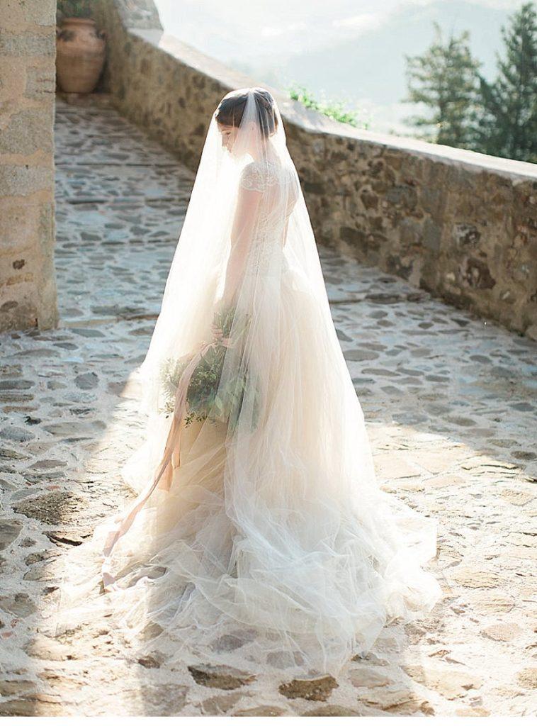 In questa foto una sposa viene ritratta sotto il suo velo mentre, filtrando la luce, si intravedono il bouquet legato da un nastro rosa, la sua acconciatura e l'ampia gonna in tulle