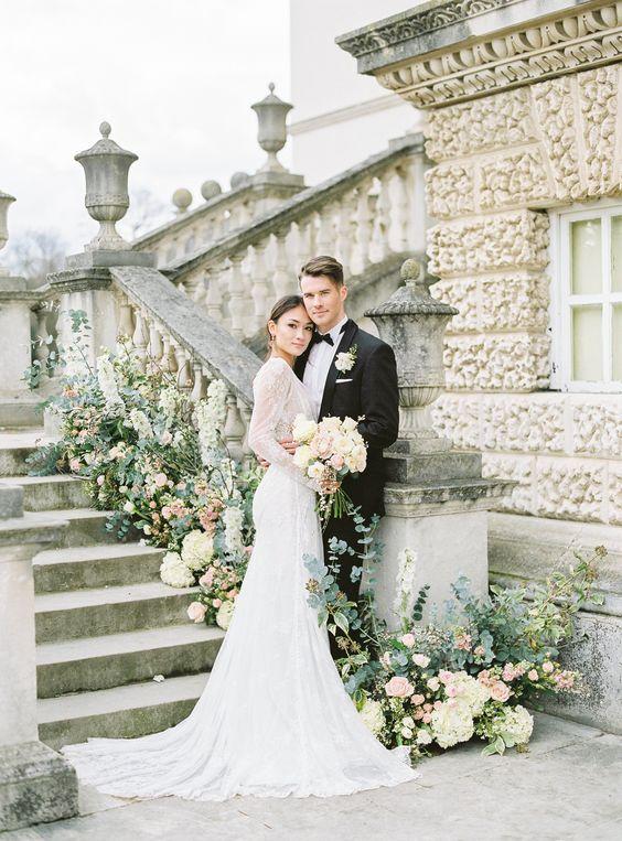 In questa foto due sposi abbracciati posano davanti ad una scalinata guardando verso il fotografo. Lei tiene in una mano il bouquet di fiori bianchi e rosa. La scalinata è decorata con fiori bianchi e rosa e foglie verdi