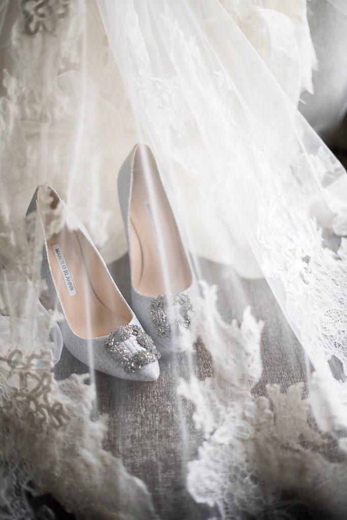 In questa foto un paio di scarpe da sposa Manolo Blanhik fotografate sotto un belo decorato con pizzo chantilly