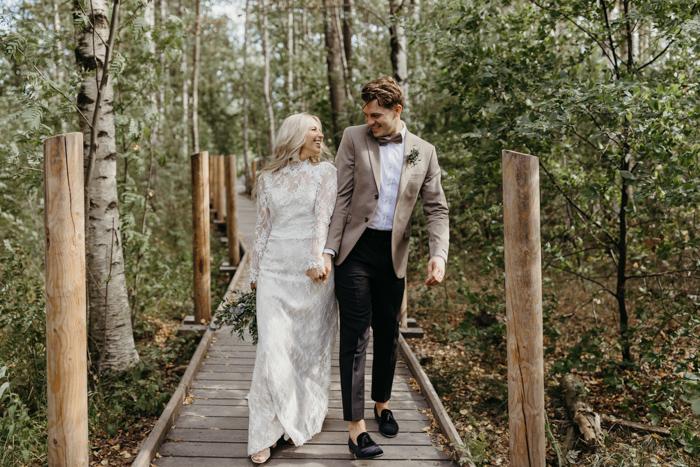 In questa foto due sposi camminano felici mentre si guardano su una pedana di legno e steccato immersa in un bosco. La sposa indossa un abito in pizzo con maniche e tiene un bouquet di felci tra le mani. Lo sposo indossa un abito spezzato marrone e beige e mocassini