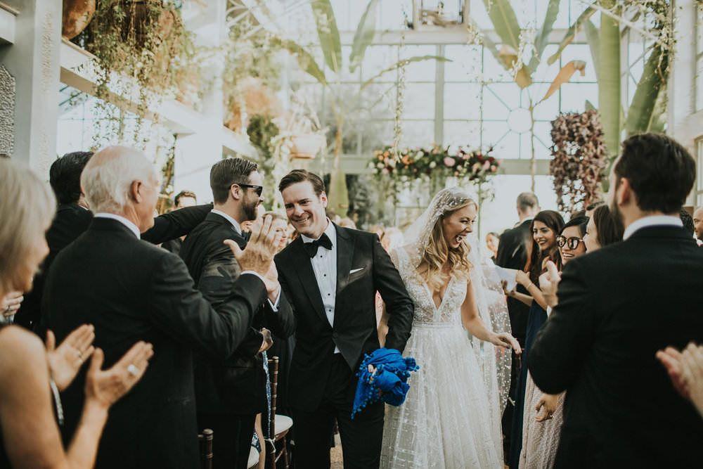In questa foto due sposi lungo la navata di una chiesa decorata con fiori escono dopo la cerimonia del loro matrimonio salutando, sorridenti, amici e parenti