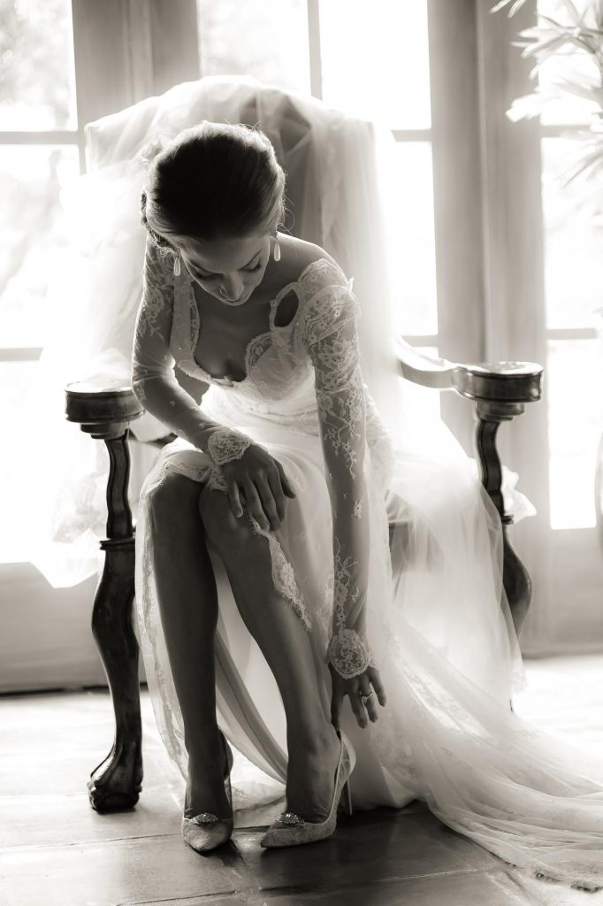 In questa foto nel color seppia una sposa mentre, seduta su una sedia con braccioli, indossa le sue scarpe
