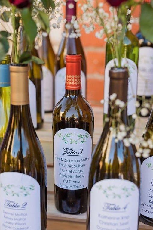 In questa foto un tableau mariage con bottiglie di vino e fiori. Sulle etichette sono riportate le liste degli ospiti divisi per tavolo