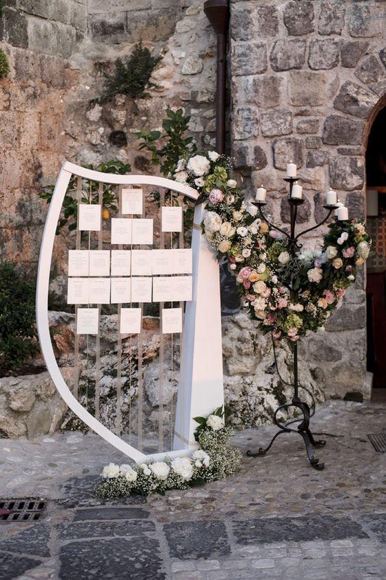 In questa foto un arpa in legno viene usata come tableau mariage a tema musica. Le card con le liste degli invitati divisi per tavolo sono appese alle corde. Completano la decorazione un grande candelabro in bronzo e allestimenti floreali in rosa e bianco