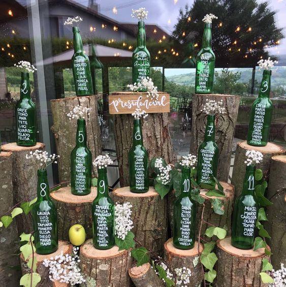 In questa foto un tableau mariage realizzato con bottiglie di birra verdi vuote su cui sono riportate le liste degli ospiti divisi per tavolo. Le bottiglie poggiate su tronchi d'albero decorati con fiori, edera e mele sono perfette per un matrimonio a tema vino