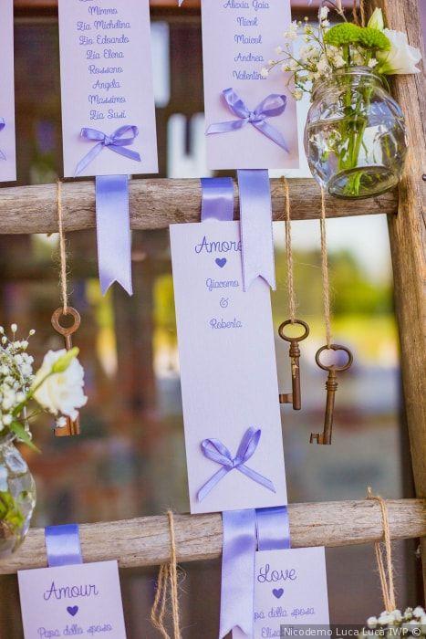 """In questa foto un tableau de mariage nel colore lilla con chiavi a forma di cuore e card con la traduzione della parola """"Amore"""" in tutte le lingue appese su una scala di legno. Vasetti con acqua e fiorellini di campo bianchi completano la decorazione"""
