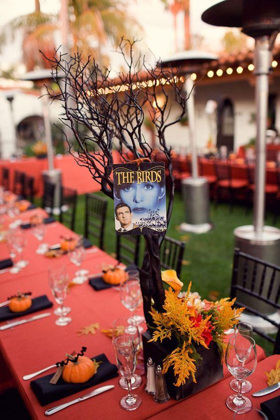 """In questa foto una mise en place per un matrimonio a tema Halloween nei colori dell'arancione e del nero. Piccole zucchette sono usate come i segnaposto a cui sono legati i nomi degli ospiti e come centrotavola un alberello secco e dei fiori arancioni a cui è applicata una piccola locandina del fil """"Gli uccelli"""" di Hitchcock"""