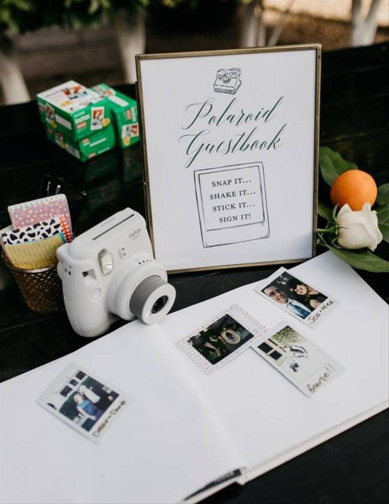 In questa foto un guestbook, un libro per gli ospiti con fotografie e una macchina Polaroid