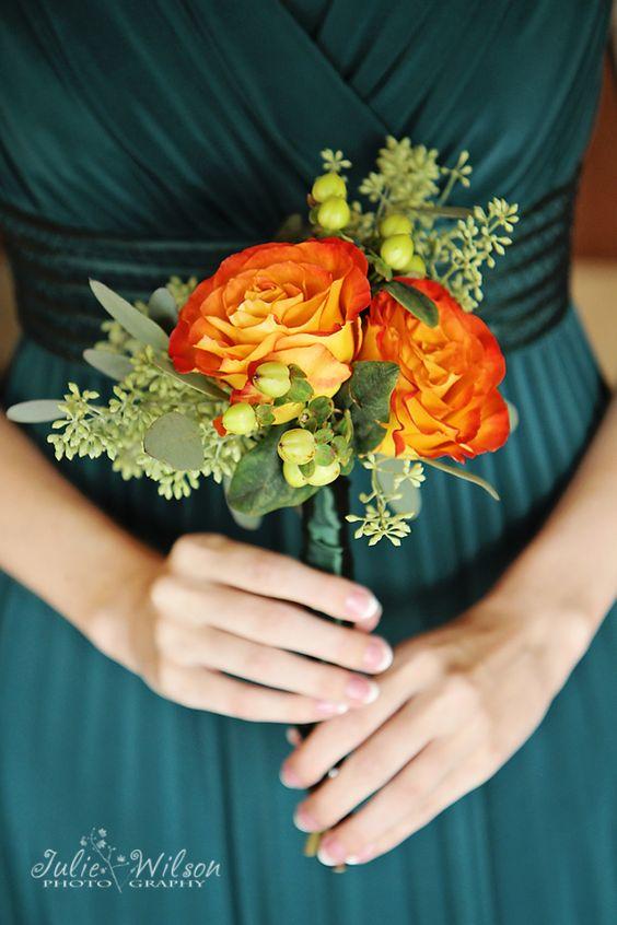 In questa foto una damigella indossa un abito verde scuro e tiene tra le mani un piccolo bouquet di rose arancioni, bacche verdi e piccole foglioline
