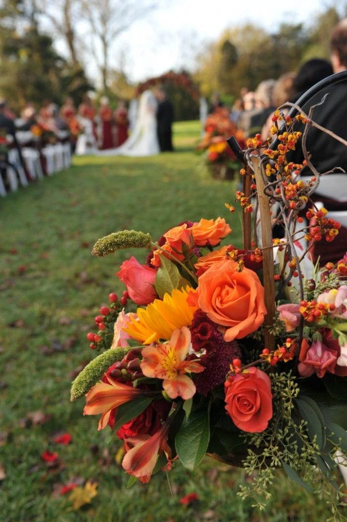 In questa foto il dettaglio di una delle composizioni floreali che decorano la navata centrale di un matrimonio all'aperto in autunno. I fiori sono abbinati in diverse tonalità di arancione e bordeaux. Sullo sfondo si intravedono, fuori fuoco, gli sposi durante le loro promesse di nozze