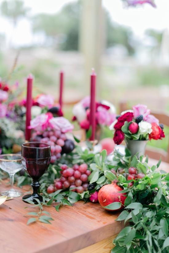 In questa foto il dettaglio di un tavolo matrimonio di legno visto in obliquo perfetto per un matrimonio a settembre. Il runner è realizzato con foglie, uva rossa, melograni e candele bordeaux. Come centrotavola sono usati vasetti di metallo con fiori di campo e ranuncoli rosa, bordeaux e bianchi