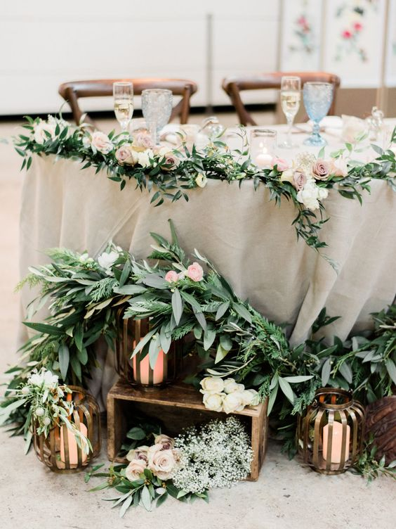 In questa foto un allestimento di nozze a tema candele e lanterne in bronzo poste alla base del tavolo degli sposi. Completano l'allestimento fasci di alloro e roselline rosa