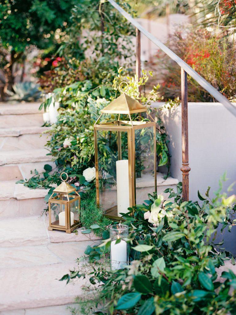 In questa foto candele dorate e candele bianche usate, insieme ad allestimenti floreali di piante e fiori bianchi, come decorazioni su una scala per un ricevimento nuziale all'aperto