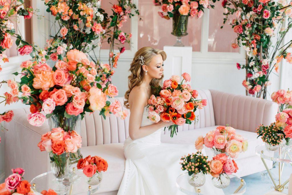 In questa foto una modella vestita da sposa posa per uno shooting fotografico a tema corallo seduta su un divano rosa e circondata da rose in tutta la stanza in coordinato.  Guarda il bouquet di rose, papaveri e ranuncoli che stringe tra le mani