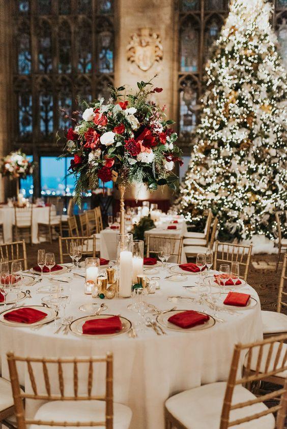 In questa foto un allestimento nuziale nei colori del bianco, del rosso, del verde e dell'oro. Sullo sfondo si intravede un albero di natale addobbato nei colori del bianco e dell'oro. Il centrotavola è realizzato con un bouquet rosso, bianco e verde poggiato su un'alzatina colore oro