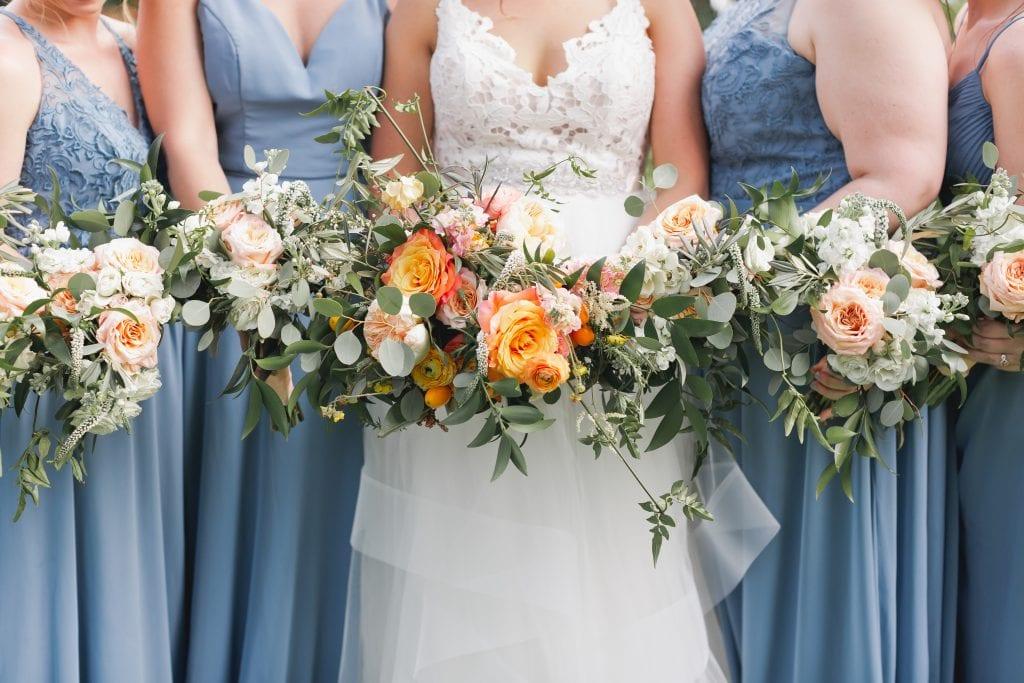 In questa foto la sposa con le sue damigelle riprese dal collo al busto tengono in mano i loro bouquet con rose arancioni e colore pesca e rametti verdi. Le damigelle indossano abiti colore azzurro polvere