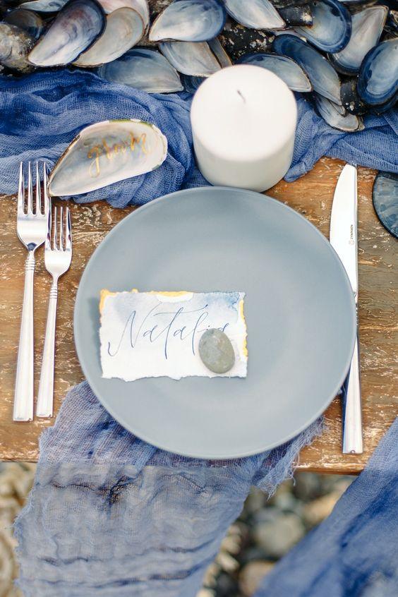 In questa foto una mise en place nei colori blu e avion allestita su un tavolo di legno nudo su una spiaggia di ciottoli. Al posto del tovagliato sono usati  runner di garza trasparente. Le posate sono in argento. Il centrotavola è realizzato con i gusci di cozze e in pendant è realizzato anche uno dei segnaposto. Il nome dell'ospite è dipinto su un cartoncino colore azzurro e oro fermato da un sassolino