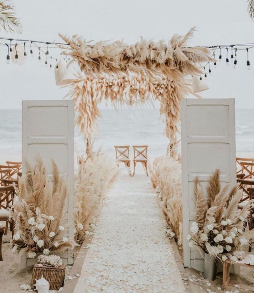 In questa foto un allestimento di un rito nuziale sulla spiaggia con pampas e fiori bianchi e avorio. Sullo sfondo sono disposte due sedie per gli sposi