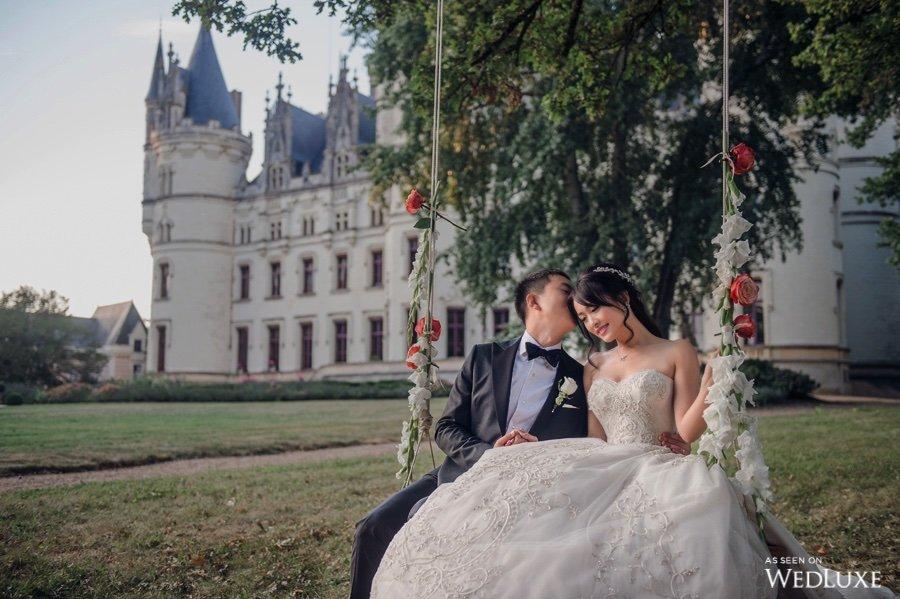 In questa foto lo sposo bacia sulla testa la sposa mentre sono seduti su un'altalena decorata con fiori bianchi e arancioni. Sullo sfondo si vede un prato e un castello
