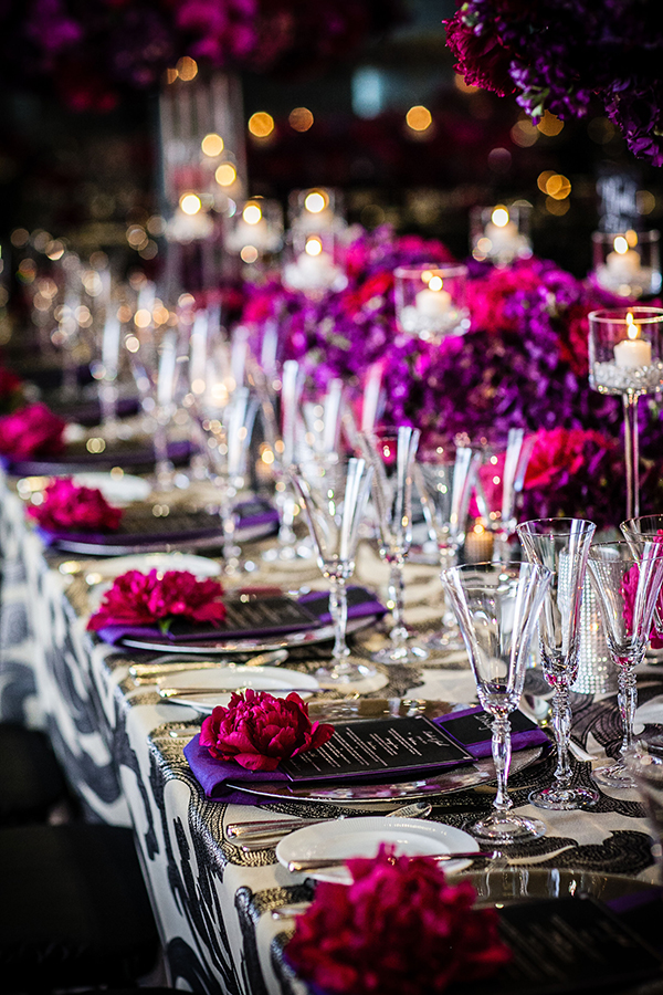 In questa foto un allestimento nuziale con ortensie nei colori del viola e del fuxia. Al tavogliato bianco e nero sono abbinati tovaglioli viola, menù neri, peonie fuxia, piatti e posate in argento, bicchieri in cristallo