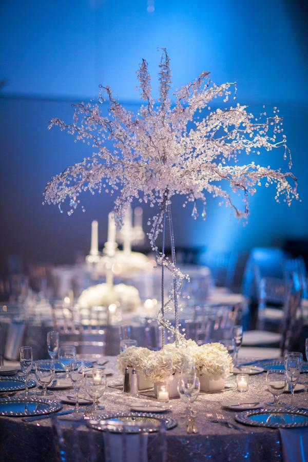 In questa foto un allestimento di nozze a tema inverno nei colori del bianco e dell'argento e del bianco. Al centro del tavolo rotondo è posta una composizione floreale di piccoli fiori bianchi e cristalli. Alla base ci sono piccoli vasetti con ortensie in pendant