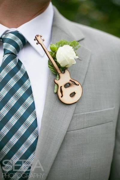 In questa foto una bottoniera su un abito grigio con una rosa bianca, rametti verdi e una piccola chitarra in legno intagliato