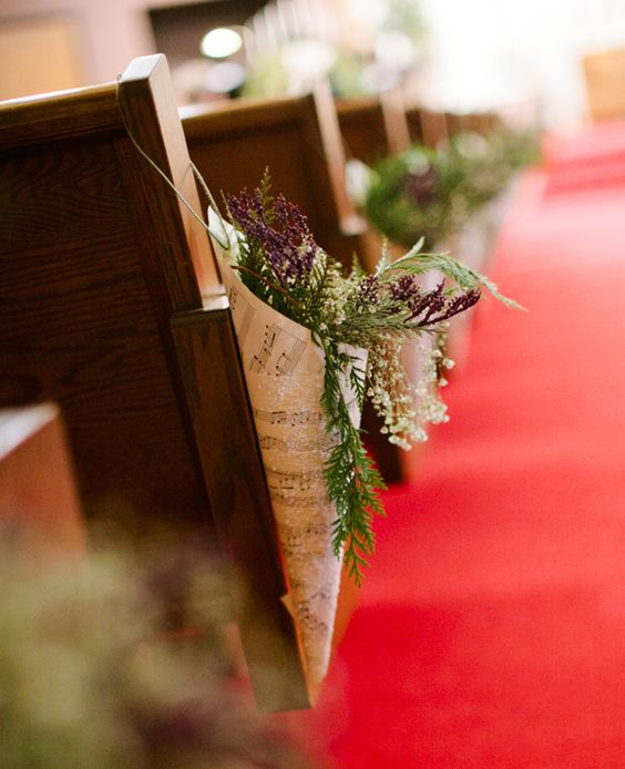 In questa foto coni realizzati con spartiti musicali e contenenti fiori di campo decorano i banchi di una chiesa allestita per un matrimonio a tema musica