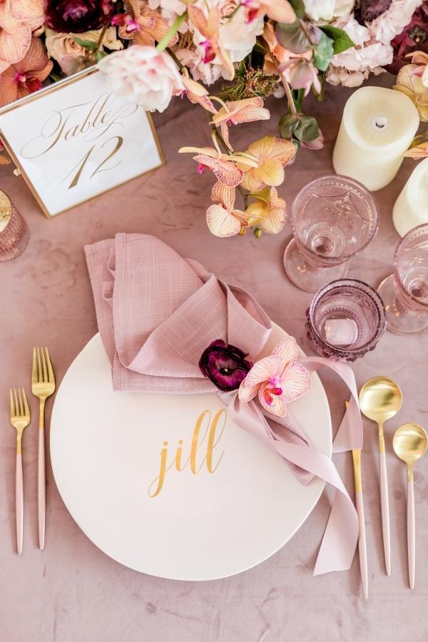 In questa foto una mise en place nei toni del lilla e dell'oro. Sul piatto bianco è poggiato un tovagliolo in lino  fermato da un nastro e due fiori