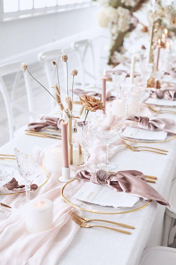 In questa foto una mise en place per un matrimonio elegante e romantico con tovaglia bianca e tovaglioli rosa antico e candele ecrù