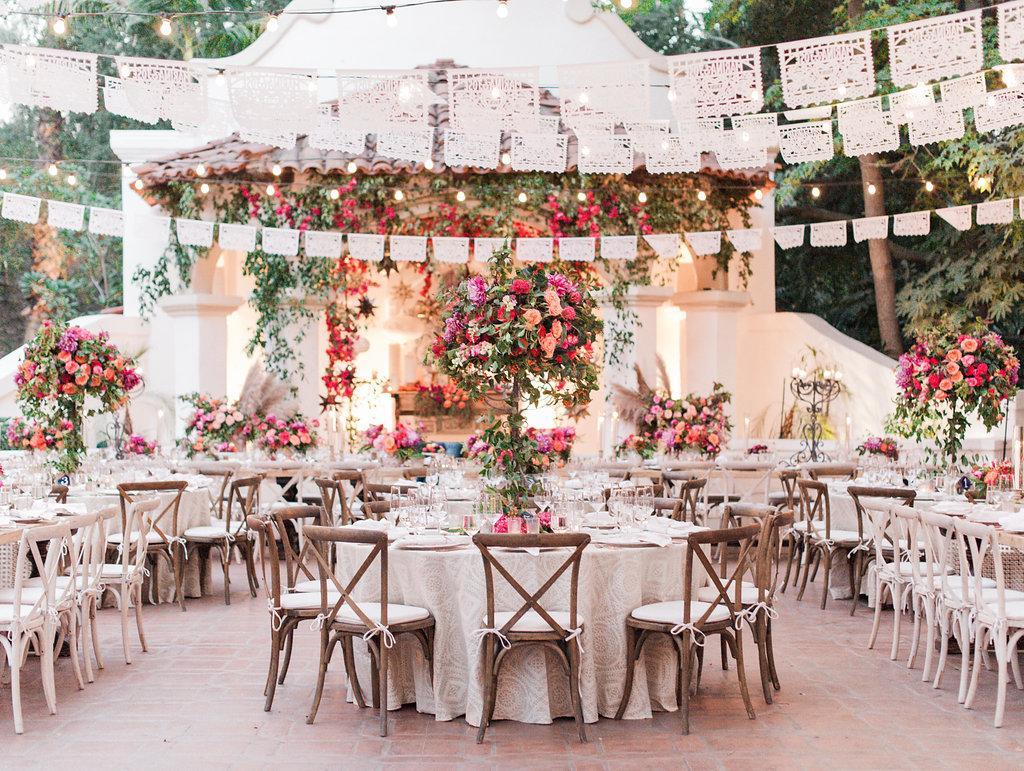 In questa foto l'allestimento di un ricevimento di nozze all'aperto in stile Boho Chic con fiori rosa, fuxia e colore pesca. I tavoli sono sormontati da festoni in pizzo bianco