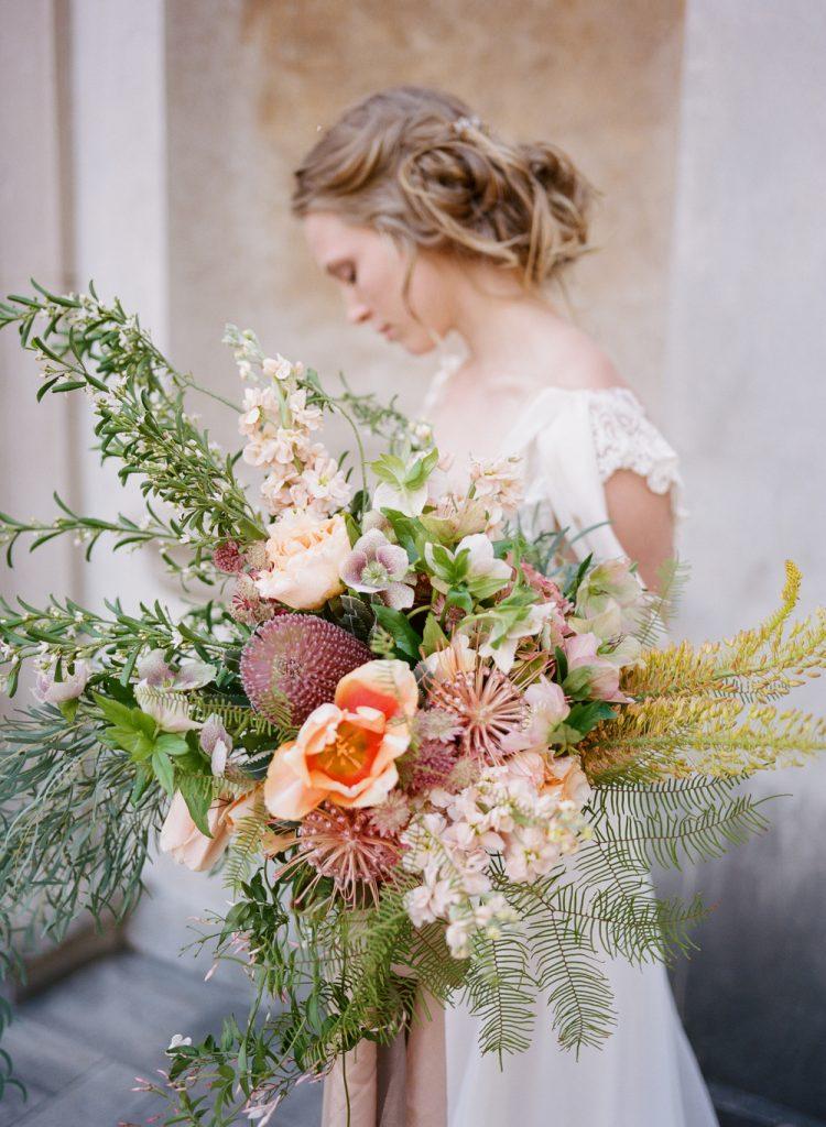 In questa foto un bouquet a bvraccio con fiori di campo, peonie, succulente e ramoscelli di ulivi e palmette