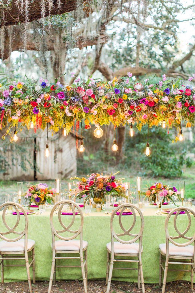 In questa foto un allestimento per un matrimonio in primavera con sedie in legno stile Shabby Chic, tovagliato colore verde pistacchio e fuxia. Come centrotavola sono usati cesti di fiori arancioni, rosa e viola. Gli stessi fiori sormontano tutto il tavolo con un arco orizzontale a cui sono legate lampadine che scendono in verticale