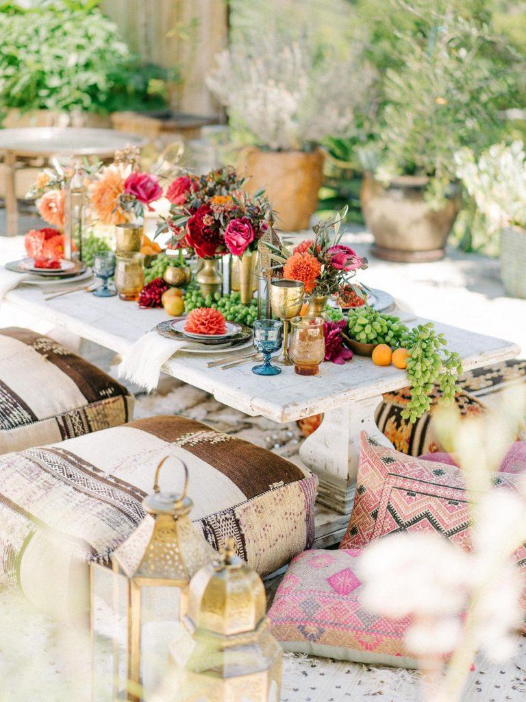 In questa foto un allestimento di un matrimonio in stile marocchino con cuscini utilizzati come sedie e lanterne dorate. Il runner del tavolo è realizzato con  frutta e fiori rossi, arancioni e fuxia. Completano le decorazioni bicchieri colorati e vasetti colore oro