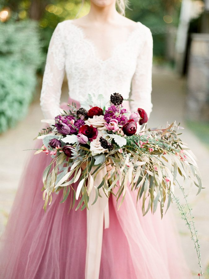 In questa foto una sposa con abito in pizzo bianco e gonna in tulle rosa tiene tra le mani un bouquet a braccio con foglie, rose rosa e rosse, tulipani rosa e ranuncoli bordeaux